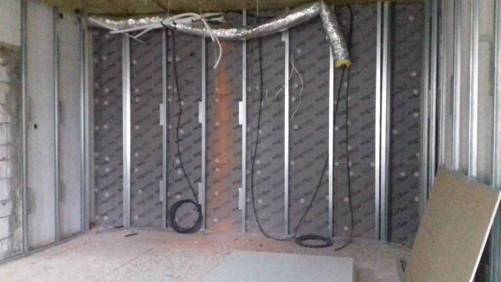 Przykład instalacji materiałów izolujących na ścianie w Łódzkiej Szkole Filmowej. Pokazane zostały instalacje, wyprowadzane na zewnątrz ściany.